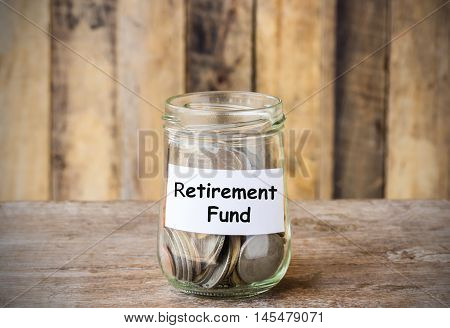 Coins in glass money jar with Retirement fund label financial concept. Vintage wooden background