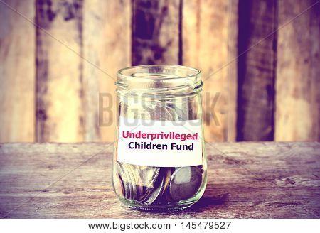 Coins in glass money jar with Underprivileged Children fund label financial concept. Vintage tone style