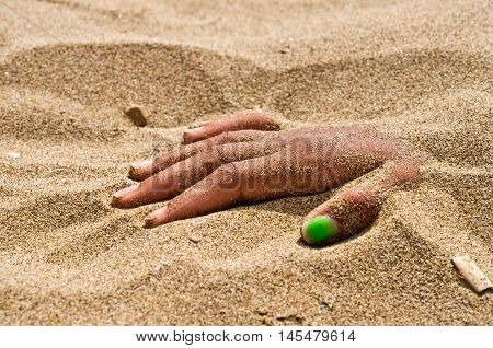 on the beach hand in rigor mortis protruding from the sand