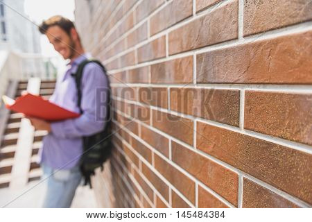 Carefree young man is reading textbook with interest. He is standing near building and smiling. Focus on wall