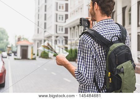 Joyful male tourist is taking photos of city. He is holding camera and map. Man is standing on street and smiling. Focus on his back