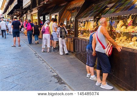 Florence Italy - July 04 2016: jewelry stores on the Ponte Vecchio with unidentified people. The medieval bridge is famous for the shops along the bridge mostly jewelers art and souvenir sellers