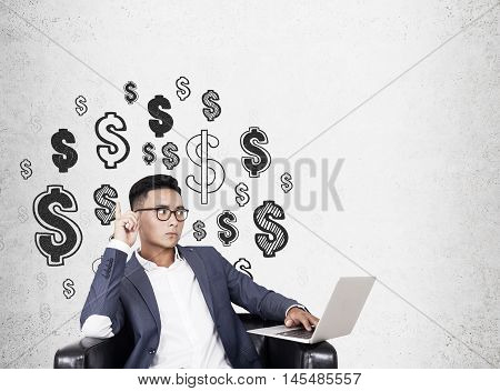 Asian businessman in armchair with notebook sitting near concrete wall with dollar sight sketches. Concept of power of money. Mock up