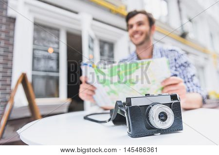 Inspired male tourist is planning route of his trip. He is sitting and holding map. Man is smiling. Focus on camera on table