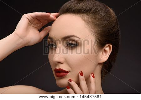 Passionate young woman is touching her face and posing with grace. She is looking forward with desire. Isolated