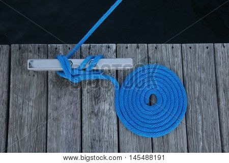 Blue rope tied to a cleat on a dock.  The rope is in a Flemish flake coiling