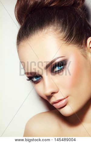 Vintage style portrait of young beautiful girl with smoky eyes make-up and hair bun