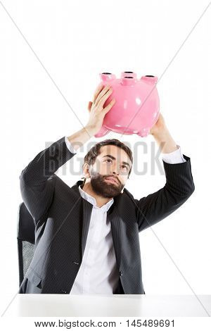 Businessman searching money in piggybank.