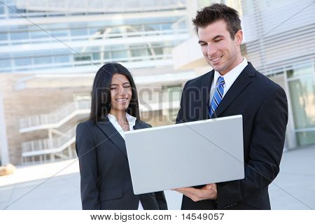 Business people in front of modern building with laptop computer