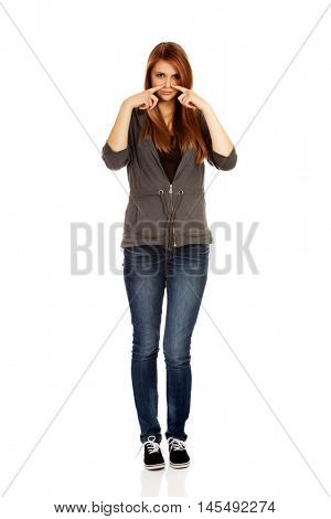 Young woman pinches nose with fingers hands looks