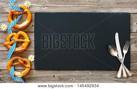 Bavarian pretzels with silverware on wooden board. Background for Oktoberfest