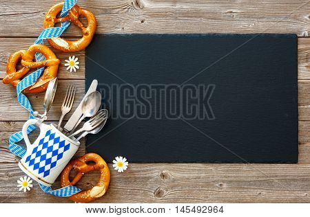 Bavarian pretzels with silverware and beer stein on wooden board. Background for Oktoberfest