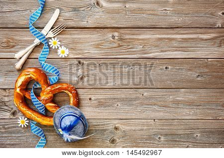 Bavarian pretzel with ribbon and silverware on wooden board. Background for Oktoberfest