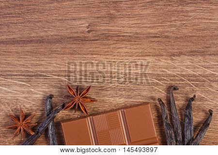 Portion of milk chocolate fresh fragrant vanilla sticks pods and star anise on wooden background copy space for text