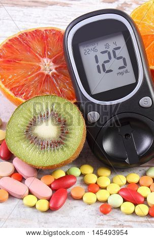 Glucometer with result of measurement sugar level fresh natural fruits and medical pills tablets and supplements concept of diabetes healthy lifestyle and nutrition