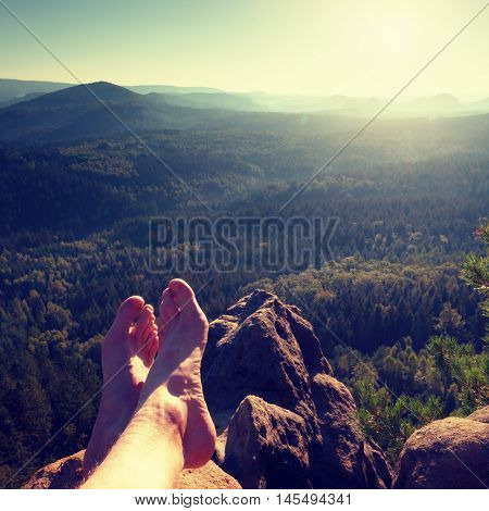 Naked male hairy legs take a rest on peak of rock. Outdoor activities in summer weather. Long forest valley in hilly landscae of nature park.