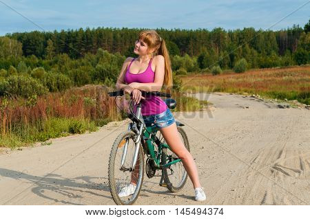 slender sexy woman on bicycle outdoors on nature