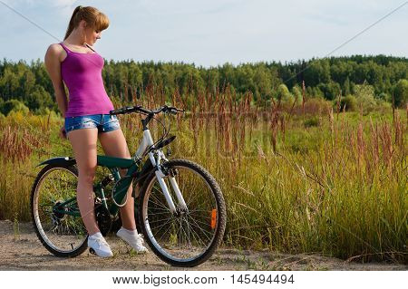 elegant woman on bicycle outdoors on nature