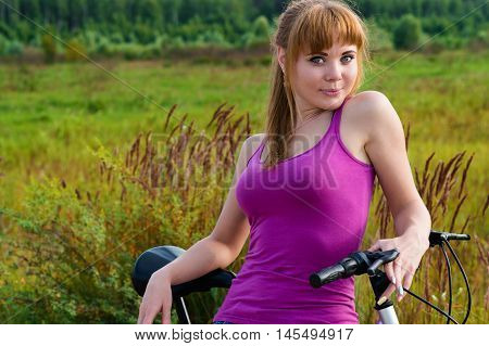 beautiful girl resting on bike on country road