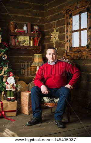 Young Man Sitting Next To Christmas Tree And Gifts