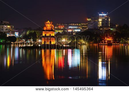HANOI, VIETNAM - DECEMBER 13? 2015: Turtle Tower and the Ngoc son temple on the background of night city's waterfront. The lake of the Returned sword the historical center of Hanoi. Historical landmark