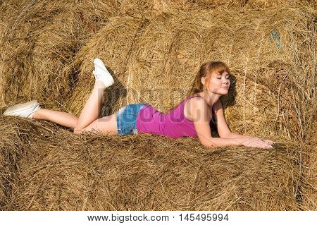 woman relaxing lying on a haystack outdoors