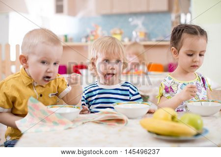 three children eating from plates in day care centre