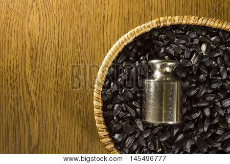 Sunflower seeds in a wicker basket and plummet on a wooden background