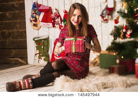 Young Girl Sitting And Unpacking Presents Next To Christmas Tree