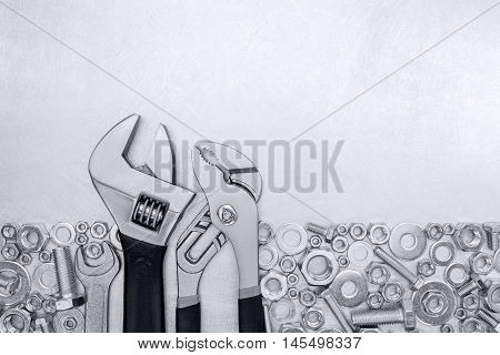 Spanner And Adjustable Wrenches With Screws And Bolts On Metal Scratched Background