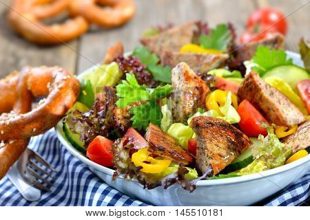 Bavarian food: Salad  with pieces of fried sausage with pig spleen served on a colorful mixed salad in a bowl
