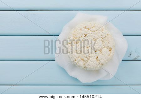 Homemade cottage cheese or curd on light blue table, rustic style, top view. Copy space for text.