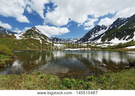 Summer landscape of Kamchatka: beautiful view of Mountain Range Vachkazhets mountain lake and clouds in blue sky on sunny day. Eurasia Russia Far East Kamchatka Peninsula.