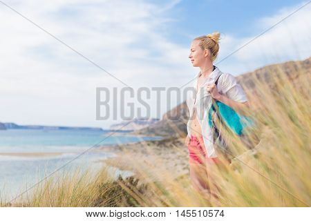 Relaxed woman on vacations in white loose shirt carrying beach bag and towel, enjoying beautiful coastline view of white sandy lagoon at Balos beach, Greece.