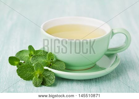 Cup of mint tea and green leaves on light table, useful and healthy herbal drink.