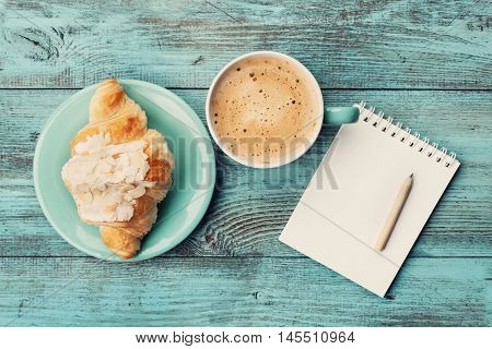 Coffee mug with croissant and empty notebook and pencil for business plan and design ideas on turquoise rustic table from above, cozy and tasty breakfast, vintage toned.