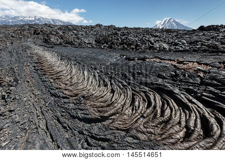 Volcanic landscape of Kamchatka Peninsula: beautiful view of lava field volcanic eruption active Plosky Tolbachik Volcano on a clear sunny weather. Eurasia Russian Far East Kamchatka Region Klyuchevskaya Group of Volcanoes.