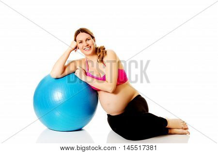 Young pregnant woman excercises with gymnastic ball.