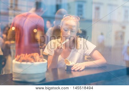 Young pretty woman eating icecream in gelateria. Through the window view.