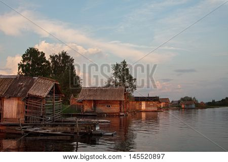 Row of bathhouses on lake in evening light