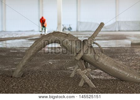 Indoor concrete floor filling process with selective focus and worker in background. Motion blur on concrete stream from pipeline.