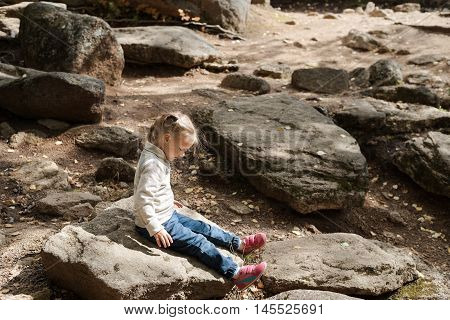 Little thoughtful girl sitting on a big stone in a summer forest. She is wearing jeans and beige sweater. It is a noon and the sunlight is harsh.