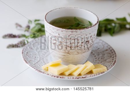 a cup of mint tea in an old mug on a saucer with cheese and a sprig of mint in the background