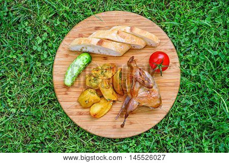 Delicious fried quail with fresh juicy vegetables on the wooden round board on green grass. Prepared tomato, cucumber, partridge, quail, slice of breads and potatos.