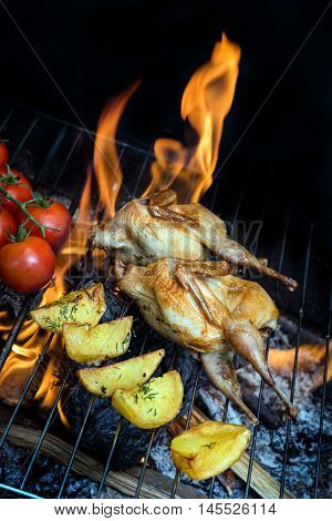 Grilling delicious poultry quails and fresh juicy vegetables in a restaurant on barbecue. Partridge, quail, potato, tomato are prepared on the grill on sunny day. Culinary concept with delicious food.