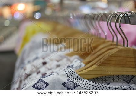 Clothes hang on a shelf in a department store.
