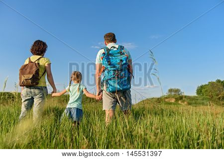 I love family time. Rear view shot of young family enjoying walk outdoors with backpacks, holding hands