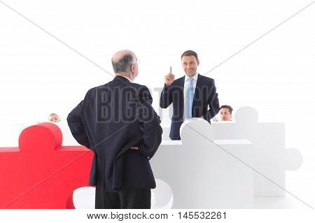 Business people hiding behind puzzle pices, isolated on white