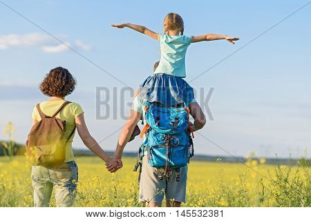 This is so much fun with dad. Little girl with pigtails sitting on father shoulders while they standing in field with her mother