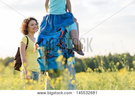 Enjoying nature together. Young family enjoying hiking across field with backpacks on their shoulders
